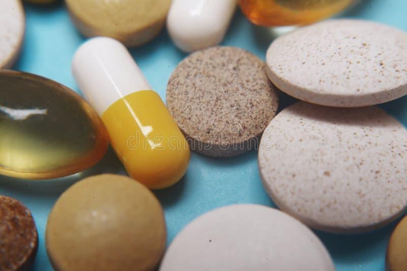P?ldoras en un fondo azul Píldoras de la medicina, tabletas y cápsulas farmacéuticas clasificadas, macro de la salud Mont?n de di fotos de archivo libres de regalías