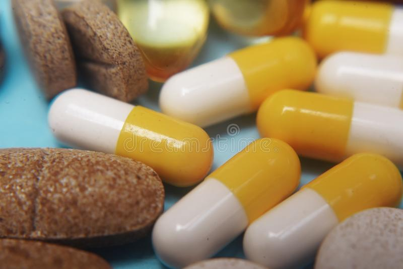 P?ldoras en un fondo azul Píldoras de la medicina, tabletas y cápsulas farmacéuticas clasificadas, macro de la salud Mont?n de di foto de archivo