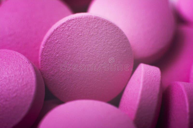P?ldoras macras Cierre para arriba Pila de muchas píldoras rosadas de la droga que ponen en una pila Fondo m?dico foto de archivo libre de regalías