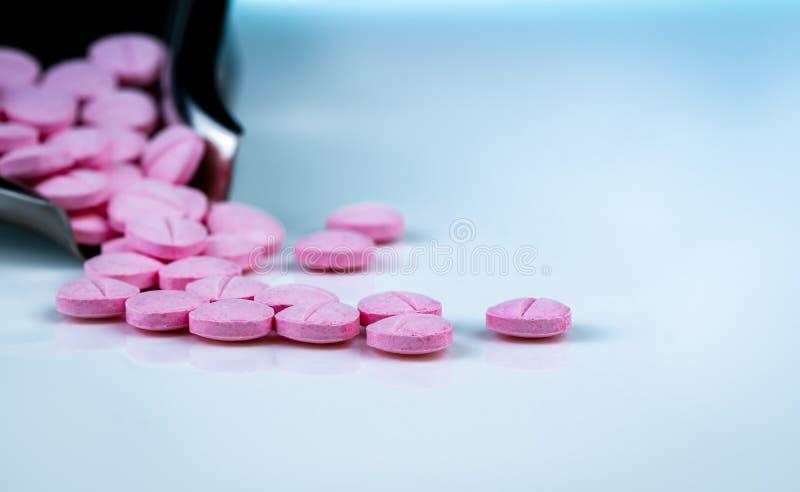 P?ldoras rosadas de las tabletas en el fondo borroso de la bandeja de la droga Industria farmac?utica Productos de la farmacia Vi fotos de archivo
