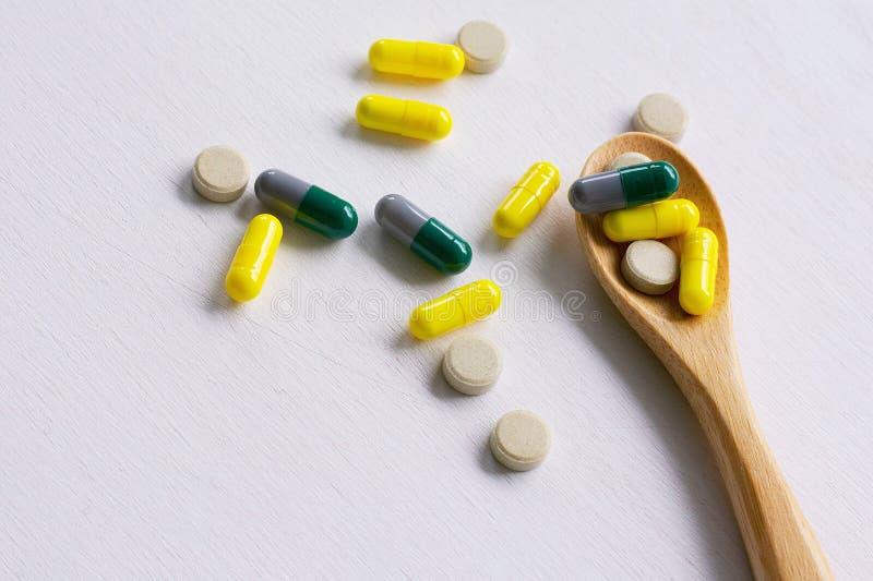 P?ldoras, tabletas y c?psulas farmac?uticas clasificadas de la medicina en la cuchara de madera foto de archivo