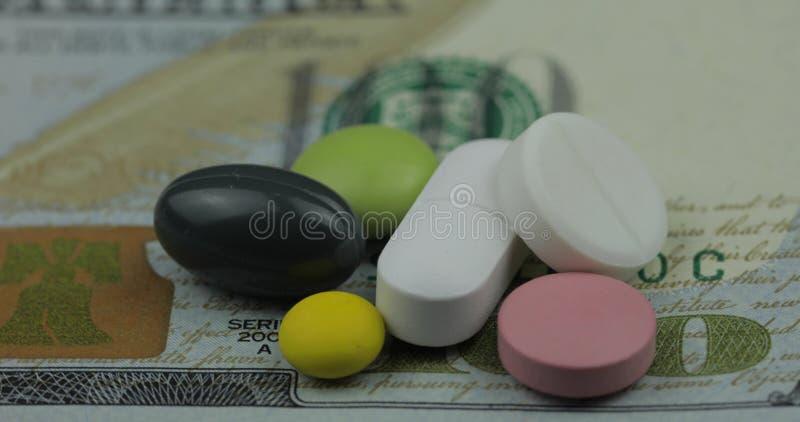 P?ldoras y tabletas m?dicas en billete de banco del d?lar Concepto farmac?utico del negocio imagen de archivo