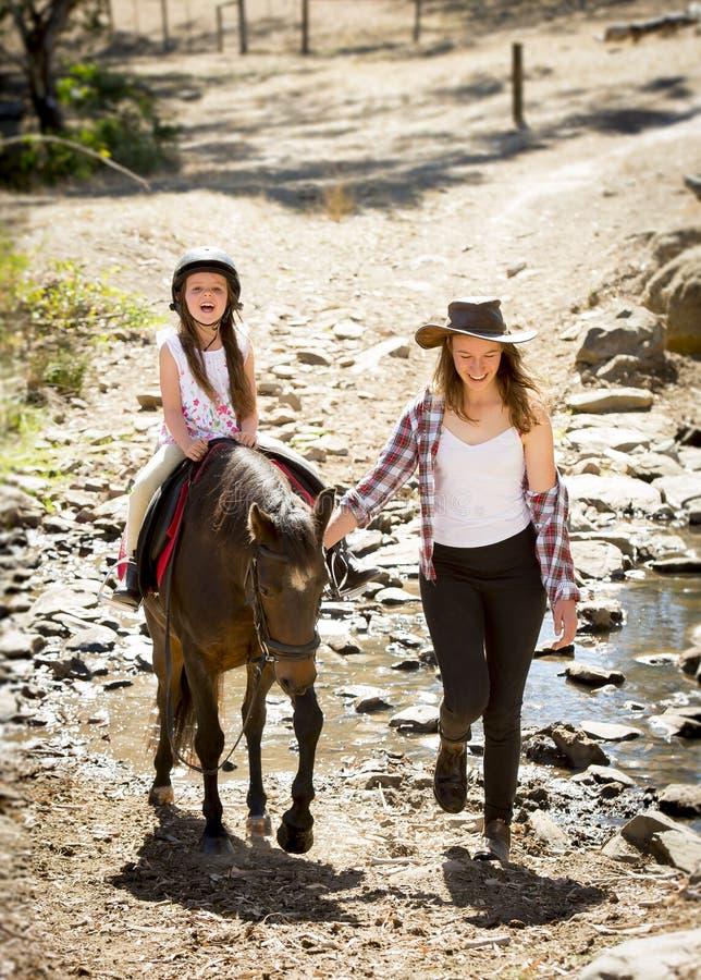 Pônei fêmea da equitação da criança do jóquei feliz com papel da mãe como o instrutor pequeno da vaqueira do cavalo fotografia de stock royalty free