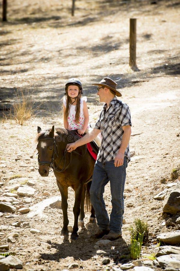 Pônei novo da equitação da criança do jóquei fora feliz com papel do pai como o instrutor do cavalo no olhar do vaqueiro imagens de stock