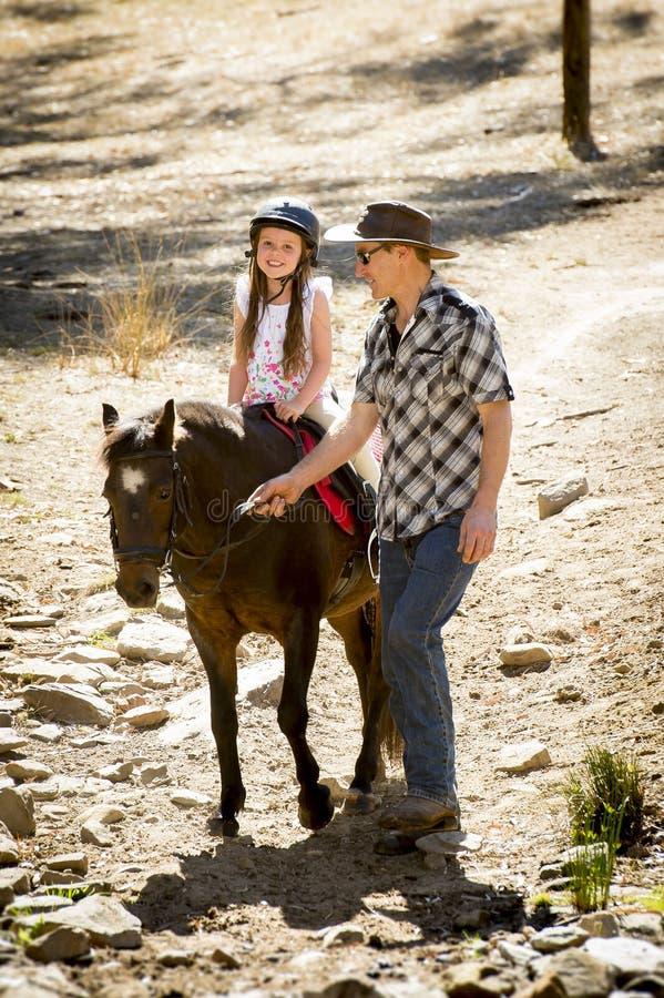 Pônei novo da equitação da criança do jóquei fora feliz com papel do pai como o instrutor do cavalo no olhar do vaqueiro fotos de stock