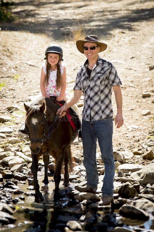 Pônei novo da equitação da criança do jóquei fora feliz com papel do pai como o instrutor do cavalo no olhar do vaqueiro fotografia de stock royalty free