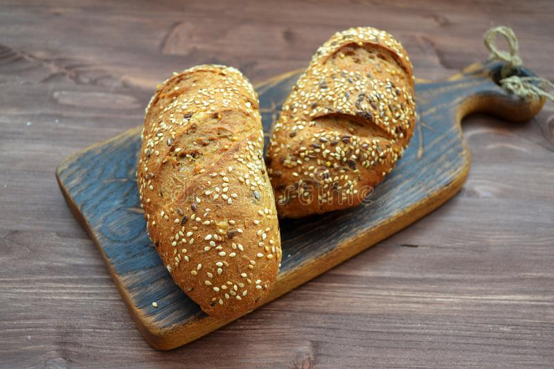P?o polvilhado com as sementes de s?samo em uma tabela de madeira O conceito do alimento biol?gico saud?vel foto de stock