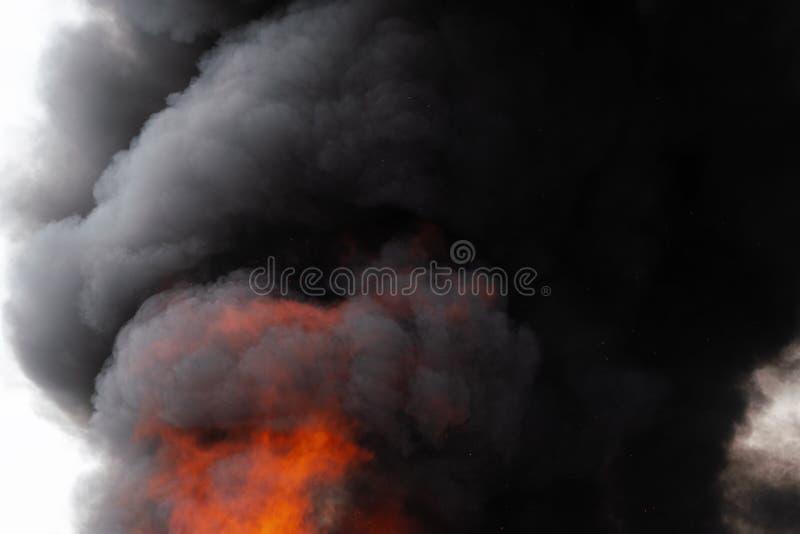P?omienie czerwonego ogienia i ruch plamy chmury czer? dym zakrywali niebo fotografia royalty free
