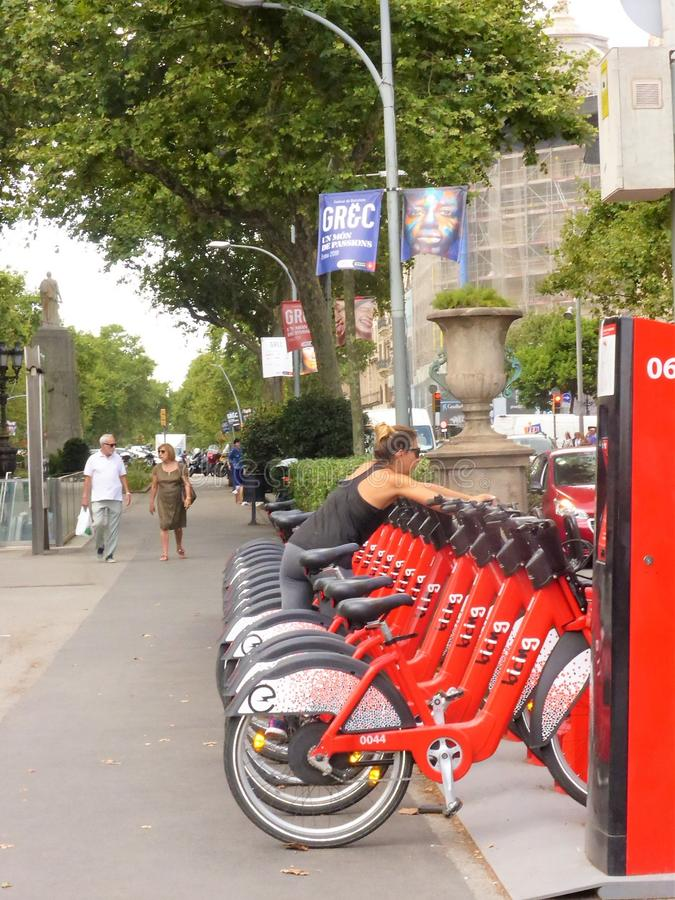 Woman getting a back from a row of electric bikes in Barcelona, Spain. Woman picking a bike from a row of red electric bikes for hire in Barcelona, Spain royalty free stock image