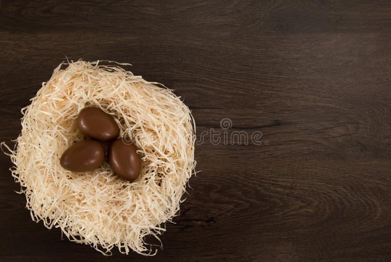 P?ques Les oeufs de chocolat se situent dans un nid sur une table brune en bois image stock