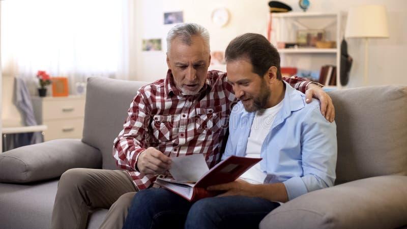 P?re adulte et fils regardant de vieilles photos partageant de bonnes traditions de famille de souvenirs images libres de droits