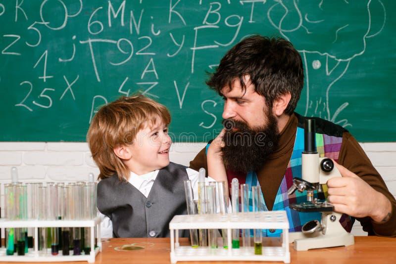 P?re enseignant sa chimie ou biologie de fils dans la salle de classe ? l'?cole homeschooling L'homme enseigne l'enfant Enfant de images libres de droits