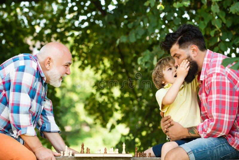 P?re et fils jouant aux ?checs Génération de famille : futur concept de rêve et de personnes Grand-père d'âge d'or photos libres de droits