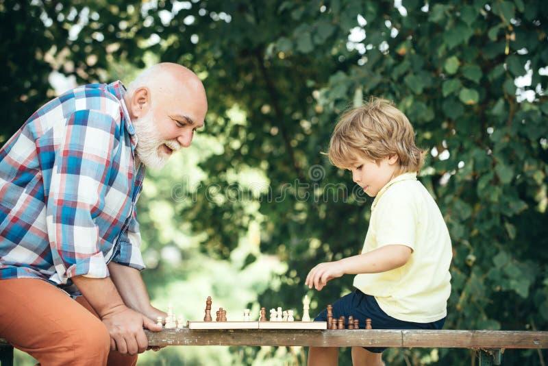 P?re et fils jouant aux ?checs Le grand-père et le petit-fils jouent des échecs et le temps de sourire de dépense de moment images stock