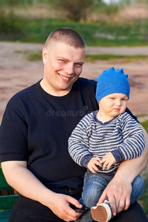 P?re joyeux s'asseyant avec son fils contrari? sur un banc en parc photos libres de droits