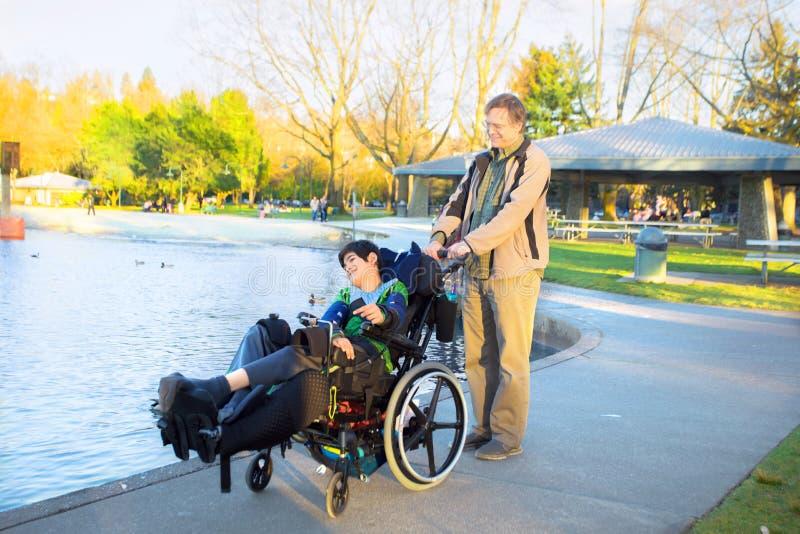 P?re marchant avec le fils handicap? dans le fauteuil roulant au parc de lac photo stock