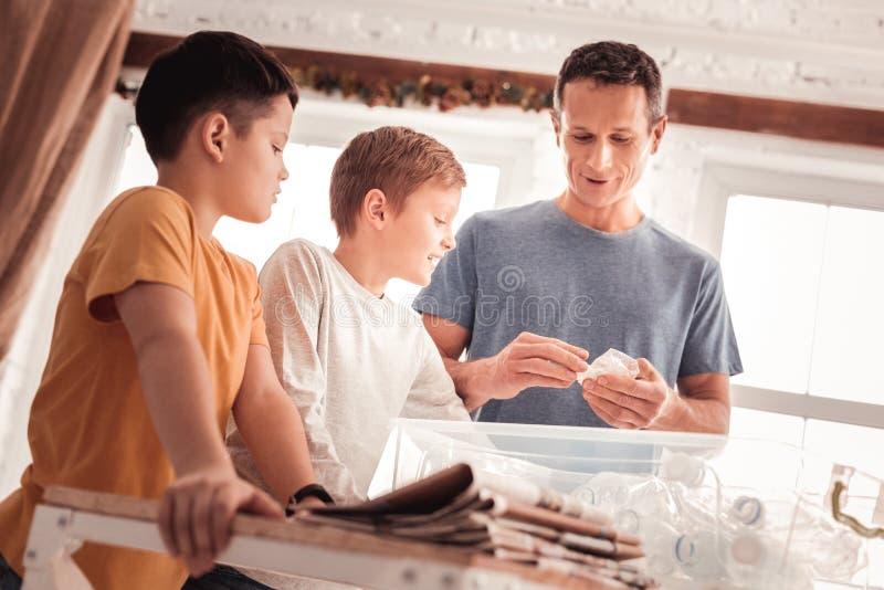 P?re utilisant la chemise bleue indiquant ses fils au sujet du tri de d?chets photographie stock libre de droits