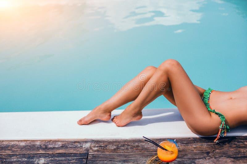 P?s bonitos da mulher Tomar sol perto da piscina fotografia de stock