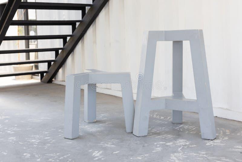 P?s cinzentos curtos e altos do tamborete de madeira ou da cadeira imagens de stock