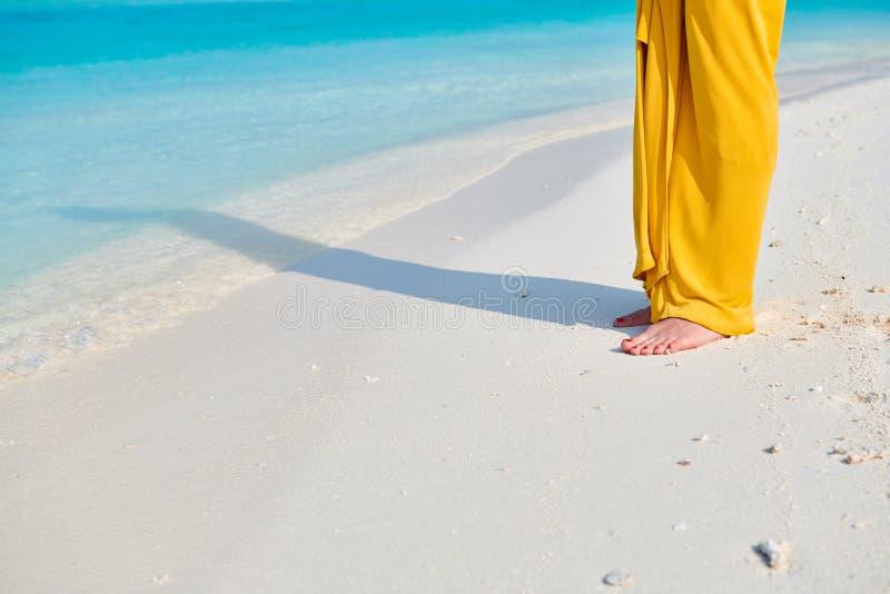 P?s da mulher no vestido amarelo na praia tropical fotografia de stock