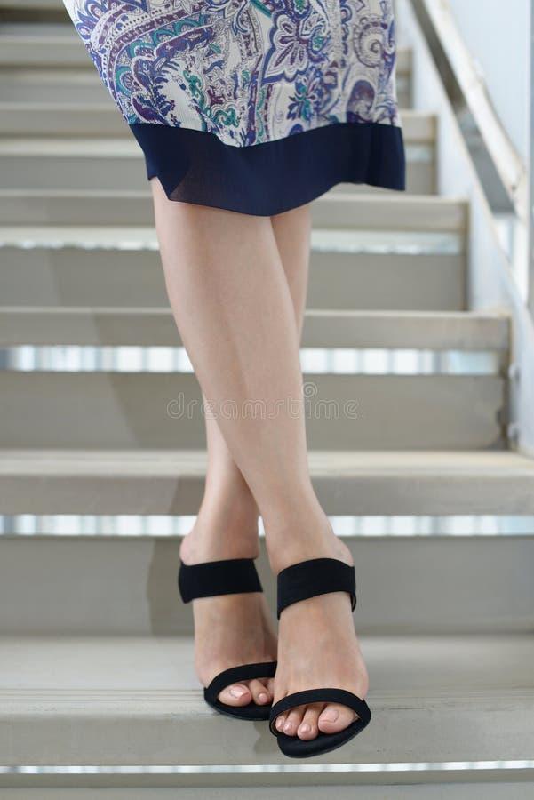 P?s da mulher que vestem sand?lias pretas do salto imagem de stock royalty free