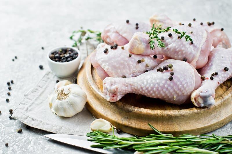 P?s de galinha crus Ingredientes para cozinhar: alecrins, tomilho, alho, pimenta Fundo do cinza, vista lateral imagens de stock