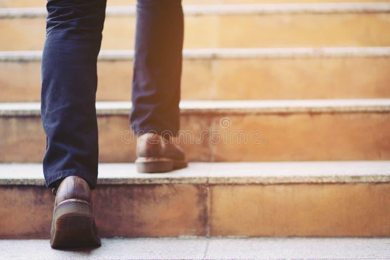 P?s de trabalho do close-up do homem de neg?cios moderno que andam acima das escadas na cidade moderna nas horas de ponta para tr imagens de stock royalty free