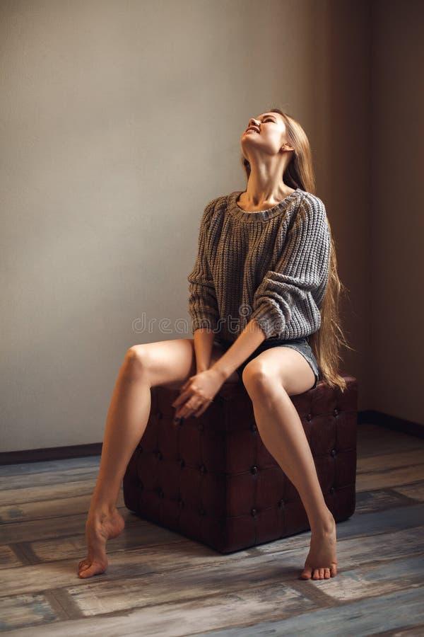 P?s longos atrativos bonitos 'sexy' e da sensualidade da mulher loura nova na camiseta morna foto de stock royalty free