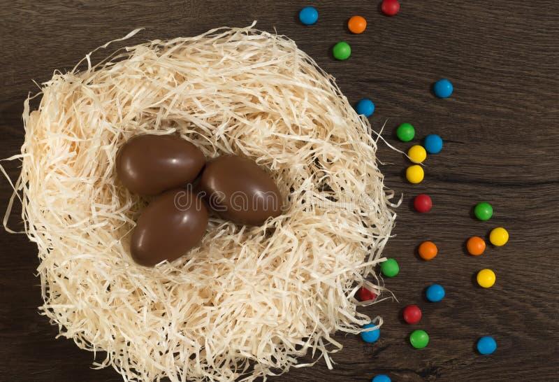 P?scoa Os ovos de chocolate com doces coloridos encontram-se em um ninho em uma tabela branca de madeira fotografia de stock royalty free