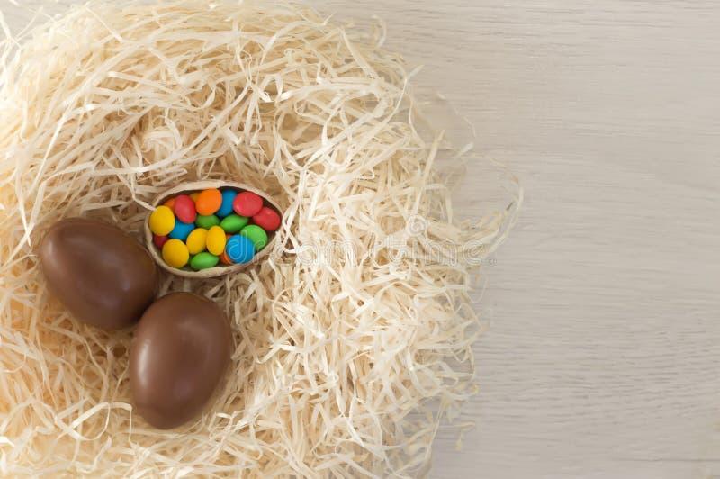 P?scoa Os ovos de chocolate com doces coloridos encontram-se em um ninho em uma tabela branca de madeira fotos de stock royalty free