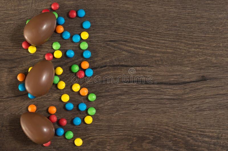 P?scoa Os ovos de chocolate com doces coloridos encontram-se em uma tabela marrom de madeira imagem de stock royalty free