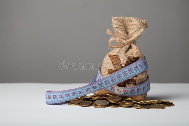 P?se med pengar och m?tabandet p? guld- mynt Brist av pengar, armod och besparingar royaltyfri bild