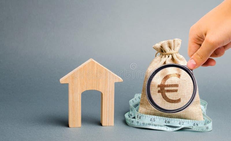 P?se med pengar och m?ttband med ett tr?hus Begreppet av en inskr?nkt fastighetbudget L?ga subventioner Brist av arkivfoto