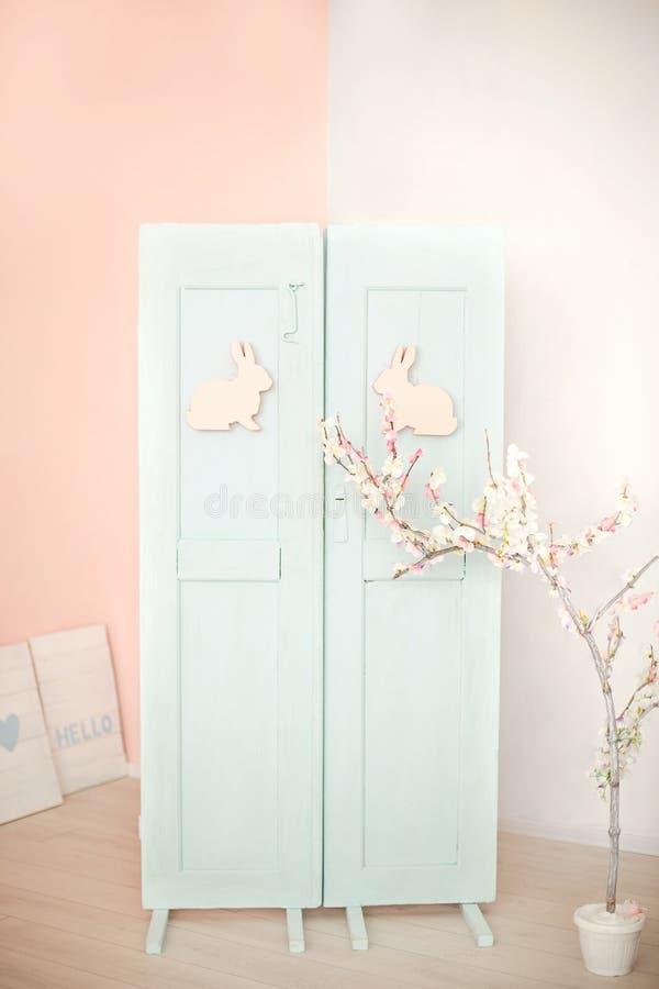 P?sk Blå dörr med den easter kaninen Garneringar på dörren med påskkaninen Lantlig inre beståndsdel av vårfarstubron Easte arkivfoto