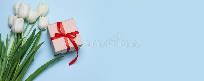 P?skdagbakgrund B?sta sikt av den vita tulpanblommabuketten, g?vaask med pappersexercins p? bl? bakgrund royaltyfri foto