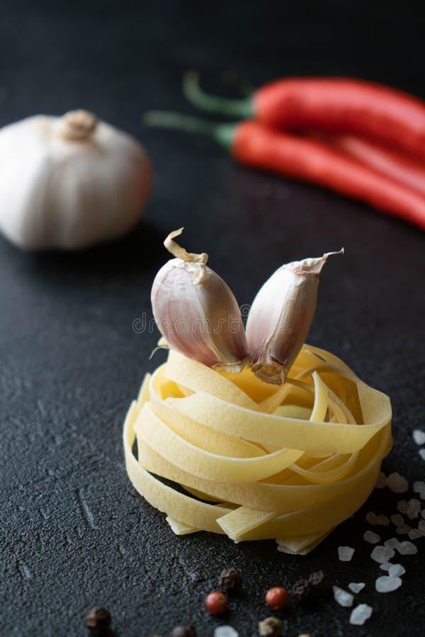 P?te crue de fettuccine avec les clous de girofle d'ail, le four de piment et les ?pices photo stock