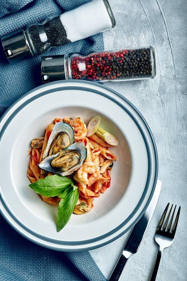 P?tes avec la sauce de fruit de mer et tomate Penne avec la crevette, poulpe, moules, Vongli en sauce tomate avec le basilic images libres de droits