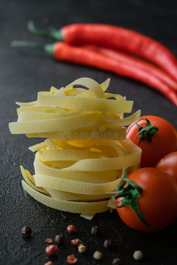 P?tes crues de fettuccine avec la tomate fra?che, les grains de poivre noirs et les poivrons de piment photographie stock