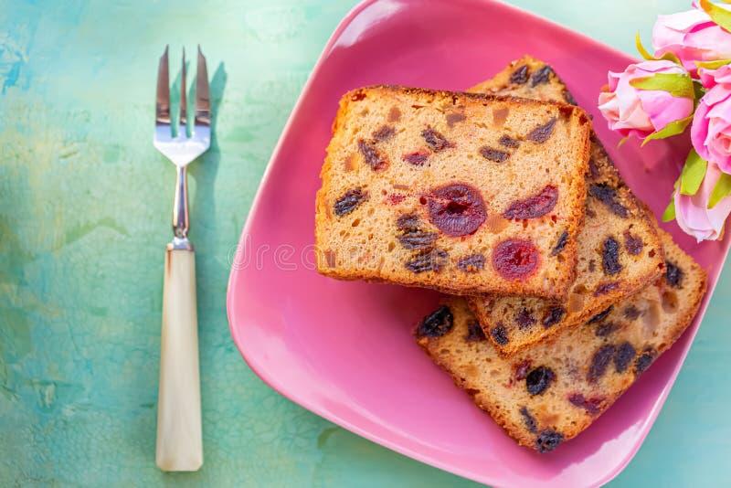 p?tisseries Une tranche de gâteau avec des fruits d'un plat rose Raisin sec et cerise de gâteau de fruit image libre de droits