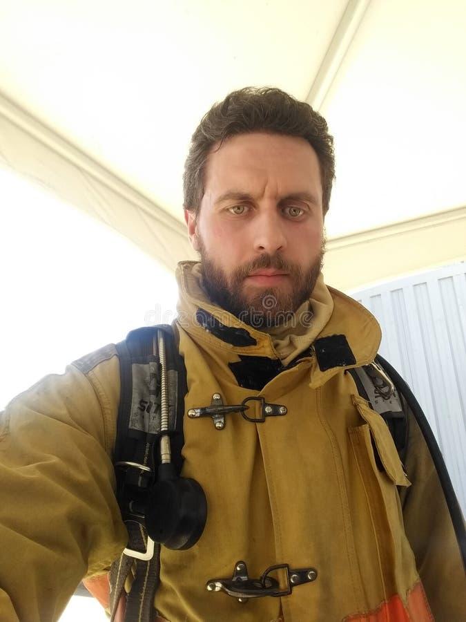 P? vakt Brandman med likformign som tar selfie Manlig jobb f?r manlighet och Manlig arbetsuppgift Allvarlig man f?r brandmanbrand arkivbilder