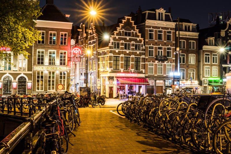 PAÍSES BAIXOS, AMSTERDÃO - 23 DE AGOSTO DE 2018: Opinião da cidade da noite da ponte de Amsterdão sobre o canal com bicicletas es imagens de stock