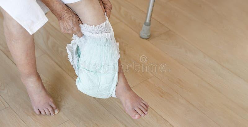 Pañal cambiante de la mujer mayor con el cuidador foto de archivo