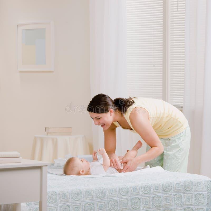 Pañal cambiante de los baby?s de la madre en cama imagen de archivo