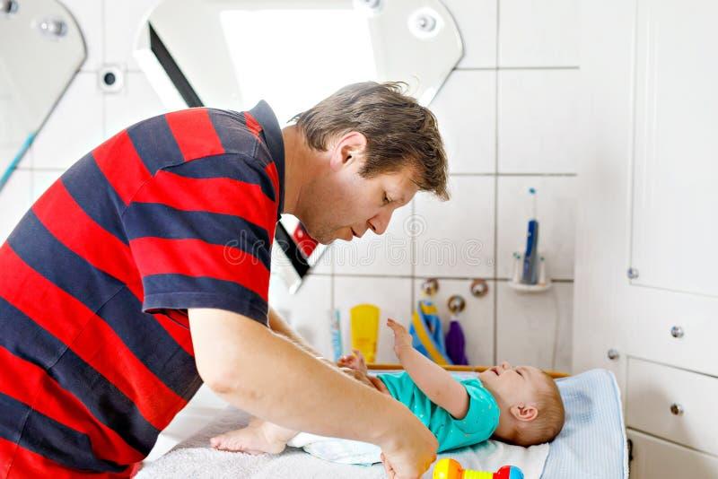 Pañal cambiante del padre cariñoso de su hija recién nacida del bebé foto de archivo