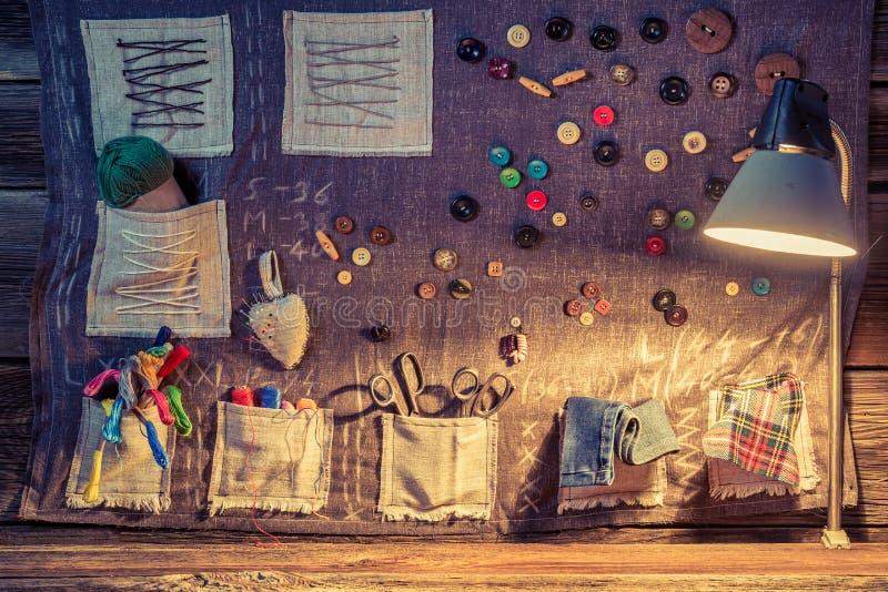 Paño de costura con las tijeras, los hilos y las agujas en taller del sastre ilustración del vector