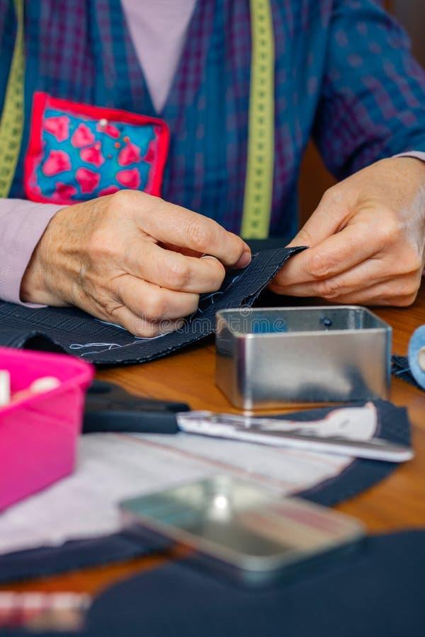 Paño de costura de la costurera de sexo femenino mayor fotografía de archivo libre de regalías