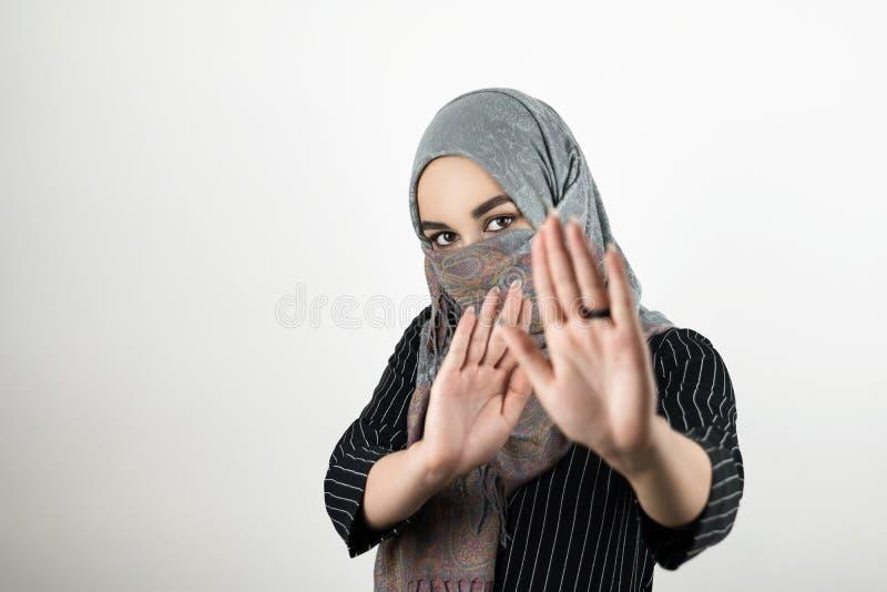 Pañuelo del hijab del turbante del estudiante que lleva musulmán atractivo joven que dice no guerrear fondo blanco aislado fotografía de archivo