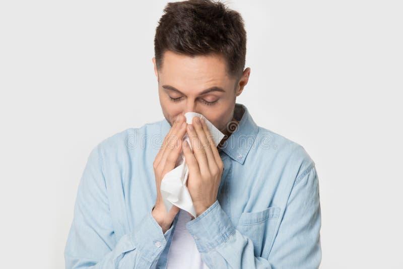 Pañuelo enfermo de la tenencia del individuo que estornuda limpiando el tiro del estudio de la nariz foto de archivo libre de regalías