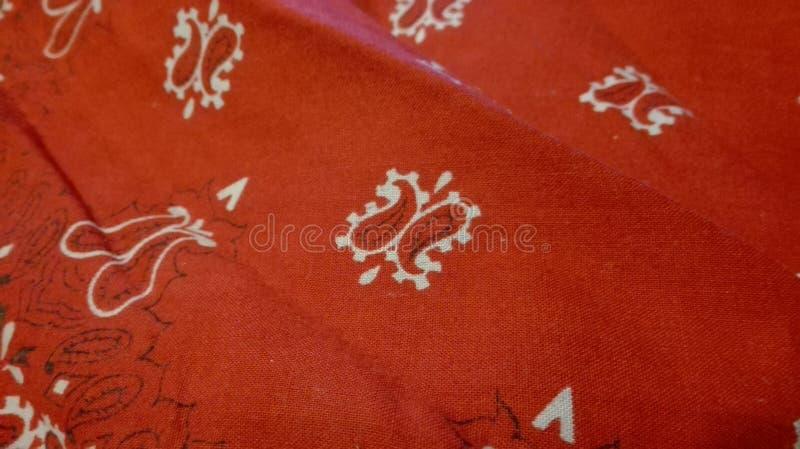 Pañuelo rojo arrugado con el bordado blanco imagenes de archivo