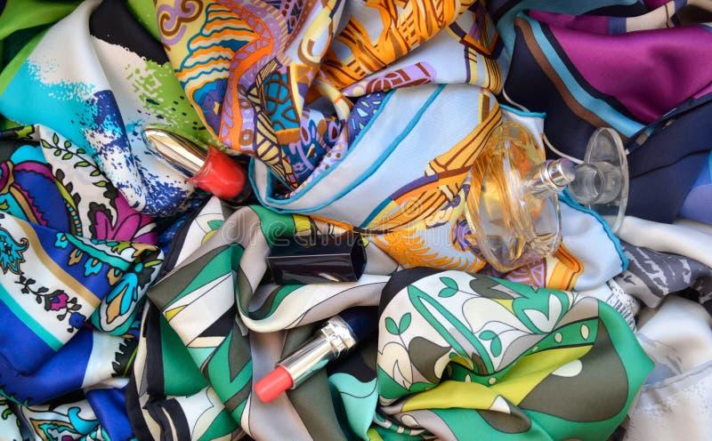 Pañuelos de seda con el lápiz labial, el perfume y el esmalte de uñas imágenes de archivo libres de regalías